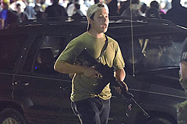 """FILE - In this Tuesday, Aug. 25, 2020, file photo, Kyle Rittenhouse carries a weapon as he walks along Sheridan Road in Kenosha, Wis., during a night of unrest following the weekend police shooting of Jacob Blake. In a document filed Thursday, Oct. 8, 2020, defense attorneys say sending Rittenhouse, accused of killing two protesters days after Jacob Blake was shot by police in Kenosha, Wis., to stand trial in Wisconsin would """"turn him over to the mob."""