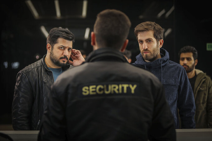 """In this undated photo provided by Shahid Avini Cultural and Artistic Institute, Iranian actors Pendar Akbari, left, and Ashkan Delavari, right, act in a scene from an episode of an Iranian TV series titled """"Gando.""""  The controversial Iranian TV spy thriller is once again generating buzz in the Islamic Republic, drawing the ire of government officials and complaints from viewers Sunday, April 4, 2021, over alleged censorship in the second season finale. The fictional series chronicles the exploits of Iran's Revolutionary Guard agents — in the style of James Bond or Jason Bourne. (Bahar Asgari/Shahid Avini Cultural and Artistic Institute via AP)"""