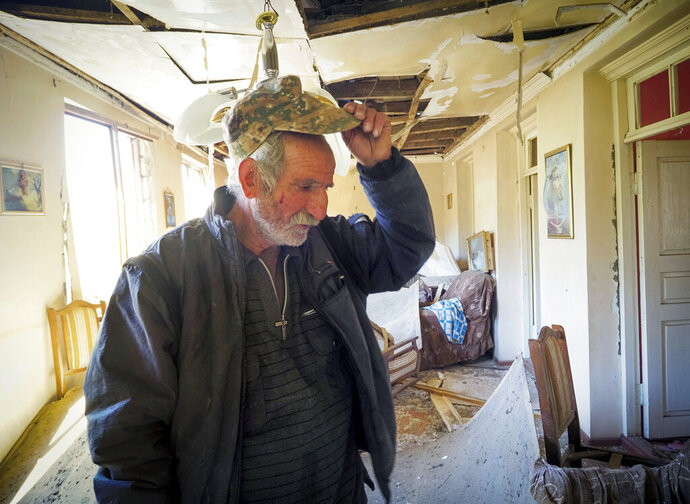 Yury Melkonyan, 64, examines his house damaged by shelling from Azerbaijan's artillery during a military conflict in Shosh village outside Stepanakert, the separatist region of Nagorno-Karabakh, Saturday, Oct. 17, 2020. The latest outburst of fighting between Azerbaijani and Armenian forces began Sept. 27 and marked the biggest escalation of the decades-old conflict over Nagorno-Karabakh. The region lies in Azerbaijan but has been under control of ethnic Armenian forces backed by Armenia since the end of a separatist war in 1994. (AP Photo)