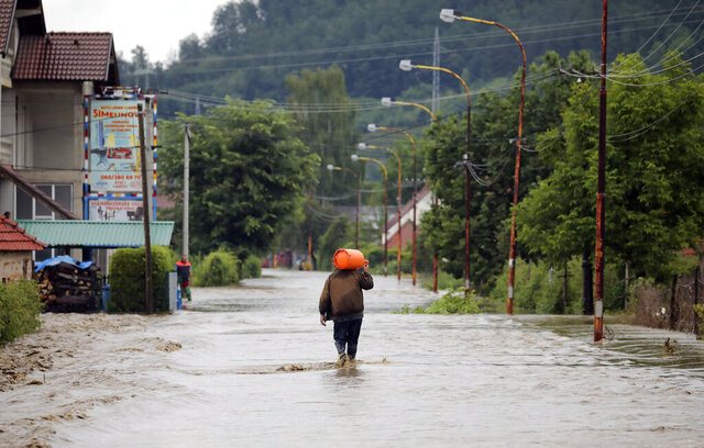 A man walks along a flooded street after heavy rain in Arilje, Serbia, Tuesday, June 23, 2020. Serbia has introduced emergency measures in several municipalities after heavy rains in the past few days caused widespread damage as rivers overflowed, authorities said Tuesday. (AP Photo/Dragan Karadarevic)