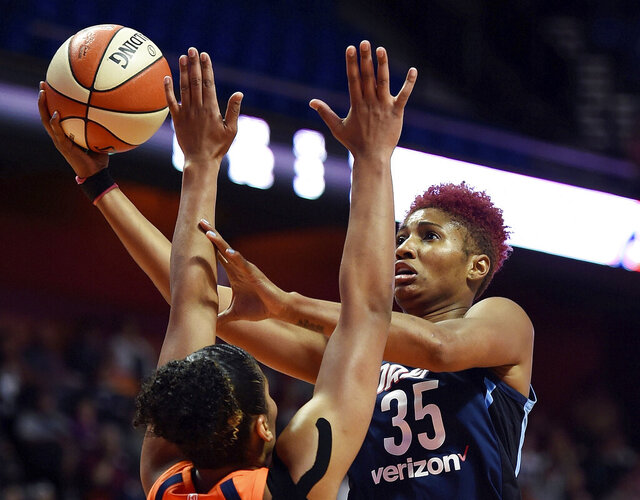 FILE - In this July 17, 2018, file photo, Atlanta Dream forward Angel McCoughtry shoots over Connecticut Sun forward Alyssa Thomas during the first half of a WNBA basketball game, in Uncasville, Conn. McCoughtry, a two-time WNBA scoring champion, is testing free agency for the first time in her career. (Sean D. Elliot/The Day via AP, File)