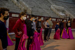 Pupils stand with their capes as they are instructed at the Bullfighting School at Las Ventas bullring in Madrid, Spain, Tuesday, Dec. 22, 2020. The school was closed from March to August when Spain went into one of the world's strictest confinements to stem the spread of the COVID-19 pandemic. (AP Photo/Manu Fernandez)
