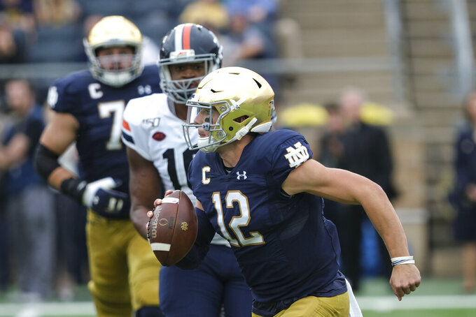 Notre Dame quarterback Ian Book (12) runs with the ball against Virginia in the first half of an NCAA college football game in South Bend, Ind., Saturday, Sept. 28, 2019. (AP Photo/AJ Mast)