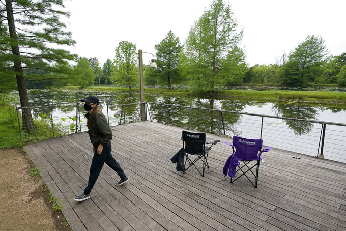 Susan Shin walks back to get her fishing pole Monday, April 20, 2020, at Sheldon Lake State Park and Environmental Learning Center in Houston. Texas Gov. Greg Abbott has ordered state parks to reopen Monday after being closed due to the COVID-19 outbreak. (AP Photo/David J. Phillip)