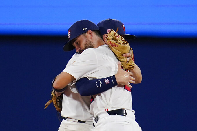 United States' Eddy Alvarez, front, and Nick Allen embrace after a semi-final baseball game against South Korea at the 2020 Summer Olympics, Thursday, Aug. 5, 2021, in Yokohama, Japan. The United States won 7-2. (AP Photo/Sue Ogrocki)