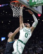 Boston Celtics forward Jayson Tatum (0) dunks against Charlotte Hornets center Willy Hernangomez, left, during the first quarter of an NBA basketball game in Boston, Wednesday, Jan. 30, 2019. (AP Photo/Charles Krupa)