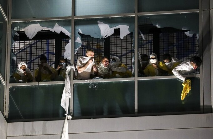 Inmates, from a second cell block, cough and try to breath through broken windows after officers deploy a chemical irritant at the St. Louis Justice Center, known as the city jail, on Sunday, April 4, 2021. Inmates broke windows, set a fire and threw debris to the ground late Sunday at a St. Louis jail that has been plagued by uprisings in recent months. (Colter Peterson/St. Louis Post-Dispatch via AP)