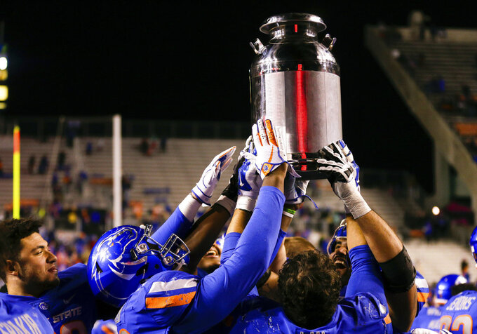 Boise State players hold up the Milk Can at the end of the game against Fresno State in an NCAA college football game, Friday, Nov. 9, 2018, in Boise, Idaho. The Milk Can goes to the winner of the annual Boise State/Fresno State game. Boise State won 24-17 over Fresno State. (AP Photo/Steve Conner)