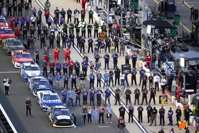 Drivers and crew members stand for the national anthem before a NASCAR Xfinity Series auto race at Bristol Motor Speedway Friday, Sept. 17, 2021, in Bristol, Tenn. (AP Photo/Mark Humphrey)