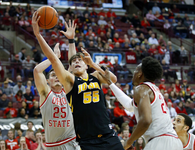 Iowa forward Luka Garza, center, goes up for a shot between Ohio State forward Kyle Young, left, and forward Andre Wesson during the first half of an NCAA college basketball game in Columbus, Ohio, Tuesday, Feb. 26, 2019. (AP Photo/Paul Vernon)