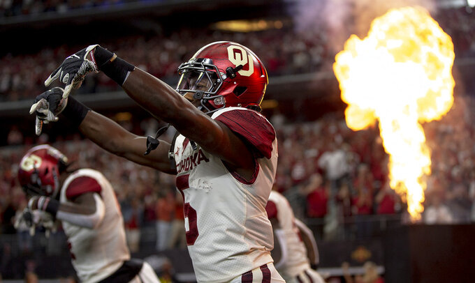 Oklahoma wide receiver Marquise Brown (5) flashes the Horns down as he takes the field before the Big 12 Conference championship NCAA college football game against Texas in Arlington, Texas, on Saturday, Dec. 1, 2018.  (Nick Wagner/Austin American-Statesman via AP)