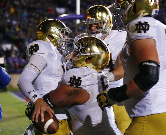 Notre Dame's Ian Book, left, celebrates his touchdown against Northwestern with teammates Aaron Banks, second left, Cole Kmet, second right, and Liam Eichenberg during the second half of an NCAA college football game Saturday, Nov. 3, 2018, in Evanston, Ill. (AP Photo/Jim Young)