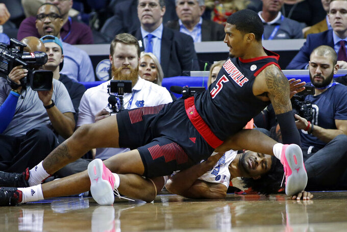 Louisville's Malik Williams (5) falls on top of North Carolina's Coby White during the first half of an NCAA college basketball game in the Atlantic Coast Conference tournament in Charlotte, N.C., Thursday, March 14, 2019. (AP Photo/Nell Redmond)