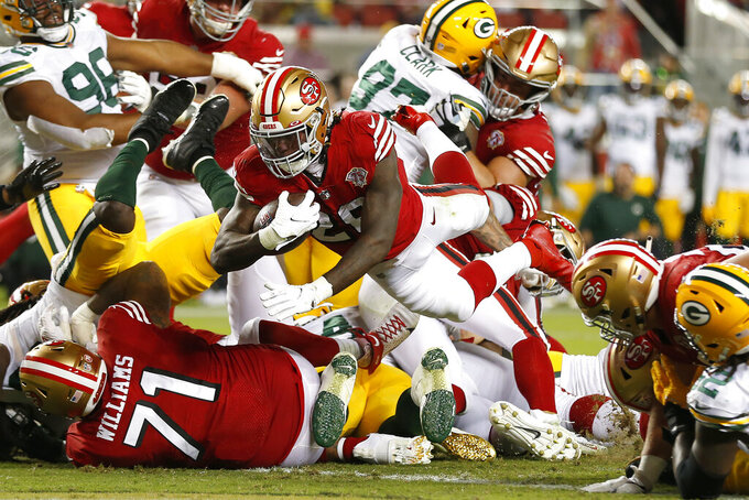 San Francisco 49ers running back Trey Sermon, middle, runs for a touchdown against the Green Bay Packers during the second half of an NFL football game in Santa Clara, Calif., Sunday, Sept. 26, 2021. (AP Photo/Jed Jacobsohn)