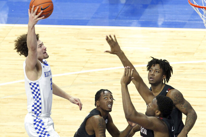 Kentucky's Devin Askew, left, shoots over South Carolina's, from left, T.J. Moss, Trae Hannibal, Wildens Leveque during the second half of an NCAA college basketball game in Lexington, Ky., Saturday, March 6, 2021. (AP Photo/James Crisp)