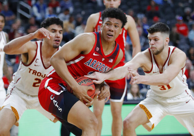 Southern California's Bennie Boatwright, left, and Nick Rakocevic, right, guard Arizona's Ira Lee during the second half of an NCAA college basketball game in the first round of the Pac-12 men's tournament Wednesday, March 13, 2019, in Las Vegas. (AP Photo/John Locher)