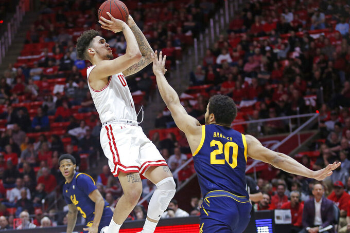 FILE - In this Feb. 8, 2020, file photo, Utah forward Timmy Allen shoots as California guard Matt Bradley (20) defends during the second half of an NCAA college basketball game in Salt Lake City. Allen is testing the NBA waters. The do-everything guard from Mesa, Ariz., joined teammate Both Gach among the 205 players on the league's most recent early-entry draft list. (AP Photo/Rick Bowmer, File)
