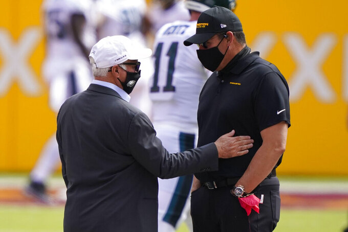 Philadelphia Eagles head coach Doug Pederson, right, talks with team owner Jeffrey Lurie, left, on the field during pregame warmups before the start of an NFL football game against Washington Football Team, Sunday, Sept. 13, 2020, in Landover, Md. (AP Photo/Alex Brandon)