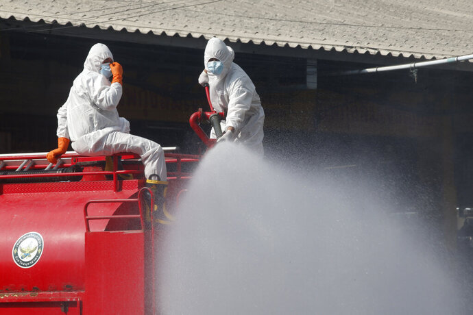 Workers spray disinfectant as a precaution against the coronavirus at a shrimp market in Samut Sakhon, Thailand, Monday, Jan. 25, 2021. Thailand on Monday registered a new daily high of over 900 confirmed new cases of the coronavirus at the province near the capital Bangkok, where a major outbreak occurred in December. (AP Photo)