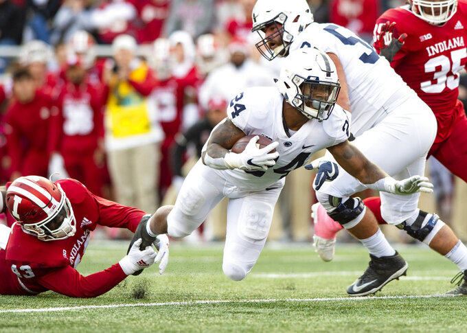 Penn State running back Miles Sanders (24) is tripped up by Indiana linebacker Dameon Willis Jr. (43) as he rushes the ball up field during the second half of an NCAA college football game Saturday, Oct. 20, 2018, in Bloomington, Ind. Penn State won 33-28. (AP Photo/Doug McSchooler)