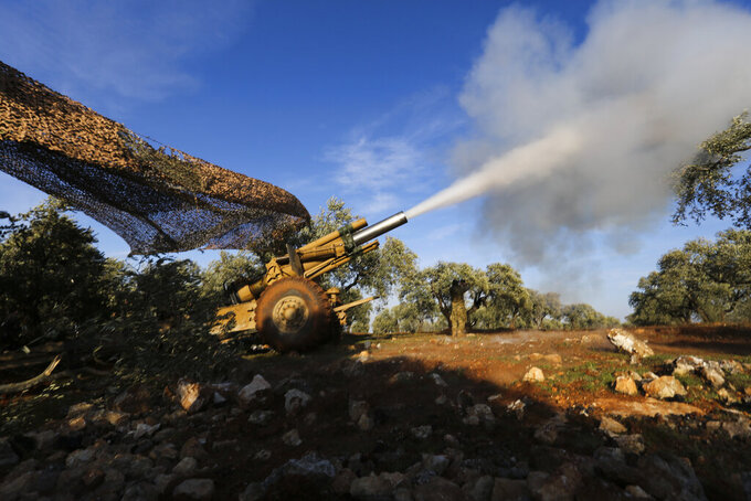 FILE - In this March 15, 2021 file photo, Turkish backed rebel fighters fire a howitzer toward Syrian government's forces positions, near the village of Neirab in Idlib province, Syria, Thursday, Feb. 20, 2020. The humanitarian situation across war-ravaged Syria is worsening. But it's been getting tougher every year to raise money from global donors to help people affected by the country's protracted humanitarian crisis. The aid community is bracing for significant shortfalls ahead of a donor conference that starts Monday, March 29, 2021, in Brussels. (AP Photo/Ghaith Alsayed, File)