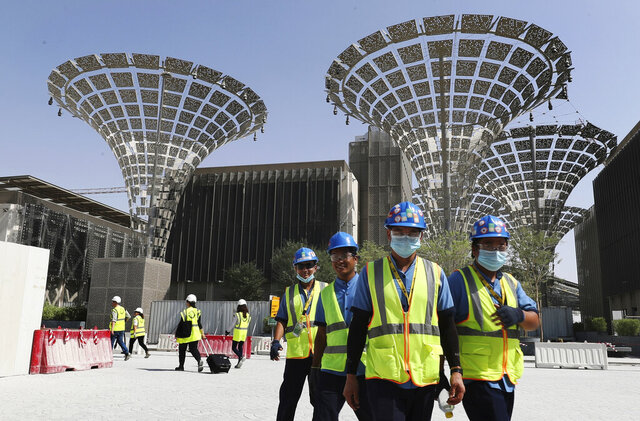 FILE - In this Oct. 8, 2019 file photo, technicians walk at the under construction site of the Expo 2020 in Dubai, United Arab Emirates. On Monday, March 30, 2020, the organizers of Expo 2020 recommended postponing the world's fair until next years over the new coronavirus pandemic. Dubai has already spent billions of dollars on the world's fair, which was supposed to take place in October. The ultimate decision over the event will be made by the Paris-based Bureau International des Expositions, which had awarded the fair to Dubai in 2014. (AP Photo/Kamran Jebreili, File)