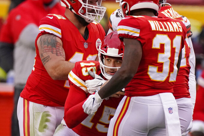 Kansas City Chiefs quarterback Patrick Mahomes (15) is helped off the field by teammates after getting injured during the second half of an NFL divisional round football game against the Cleveland Browns, Sunday, Jan. 17, 2021, in Kansas City. (AP Photo/Charlie Riedel)