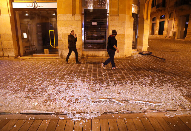 Lebanese men pass in front of a coffee shop that was smashed by anti-government protesters, during a protest against the new government, in downtown Beirut, Lebanon, Wednesday, Jan. 22, 2020. Lebanon's new government, made up of members nominated by the Shiite group Hezbollah and its allies got down to business Wednesday, a day after it was formed. Questions arose immediately about its ability to halt a spiral of economic and political collapse. (AP Photo/Hussein Malla)