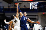 Connecticut's Tyrese Martin (4) goes up for a shot against Villanova's Caleb Daniels (14) during the second half of an NCAA college basketball game, Saturday, Feb. 20, 2021, in Villanova, Pa. (AP Photo/Matt Slocum)