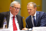 European Commission President Jean-Claude Juncker, left, and European Council President Donald Tusk, right, speak with each other during a tripartite summit in Brussels, Wednesday, Oct. 16, 2019. European Union and British negotiators have failed to get a breakthrough in the Brexit talks during a frantic all-night session and will continue seeking a compromise on the eve of Thursday's crucial EU summit. (AP Photo/Virginia Mayo)