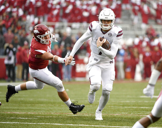 FILE - In this Nov. 18, 2017, file photo, Mississippi State quarterback Nick Fitzgerald slips past Arkansas defender Grant Morgan to score a touchdown during the first half of an NCAA college football game in Fayetteville, Ark. Mississippi State plays Kansas State this week; Fitzgerald did non play in the team's opening game last week. (AP Photo/Michael Woods)