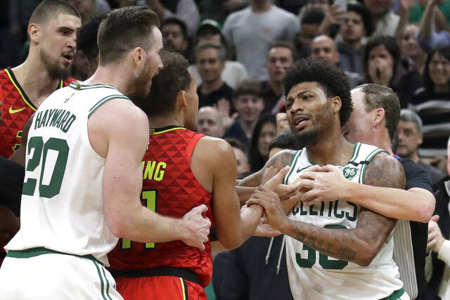 Boston Celtics guard Marcus Smart, right, is held back by a referee as Celtics forward Gordon Hayward (20) holds Atlanta Hawks guard Trae Young (11) during a scuffle in the last seconds of an NBA basketball game Friday, Jan. 3, 2020, in Boston. The Celtics won 109-106. (AP Photo/Elise Amendola)