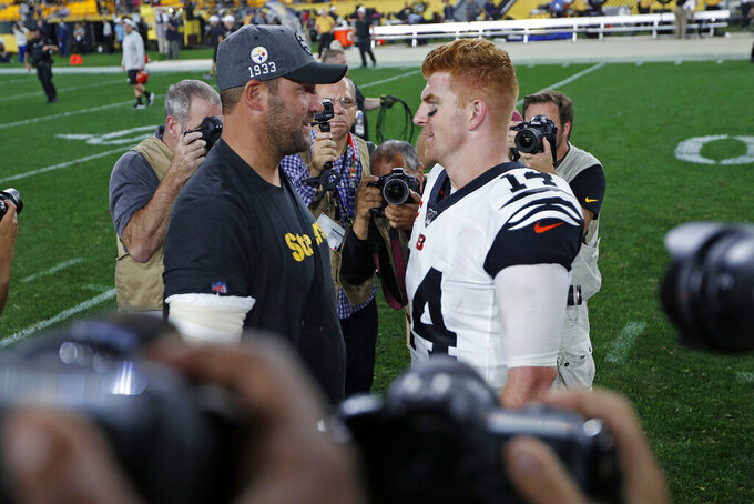 Injured Pittsburgh Steelers quarterback Ben Roethlisberger, left, and Cincinnati Bengals quarterback Andy Dalton (14) meet on the field following an NFL football game in Pittsburgh, Monday, Sept. 30, 2019. (AP Photo/Tom E. Puskar)