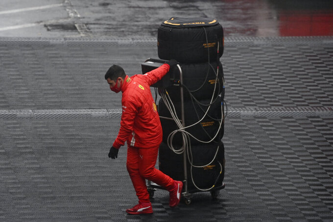 A Ferrari mechanic pulls a set of tires on the paddock before the second practice session for the Eifel Formula One Grand Prix at the Nuerburgring racetrack in Nuerburg, Germany, Friday, Oct. 9, 2020. The Germany F1 Grand Prix will be held on Sunday. (Ina Fassbender, Pool via AP)