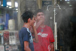 People cool off from the summer heat under an open air shower on a street in Baghdad, Iraq, Sunday, July 5, 2020. (AP Photo/Hadi Mizban)