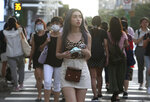 People walking thorough the streets of downtown Taipei, Taiwan, with face masks to help curb the spread of the coronavirus, Friday, June 19, 2020. (AP Photo/Chiang Ying-ying)