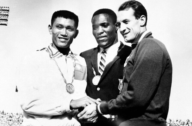 FILE - In this Sept. 7, 1960, file photo, Rafer Johnson of Kingsburg, Calif., is flanked by runners-up, Chuan-Kwang Yang, left, of Taiwan, and Vasily Kuznetsov of Russia, as they join in three-way handshake after receiving medals for the decathlon event of the Olympics in Rome, Italy. Rafer Johnson, who won the decathlon at the 1960 Rome Olympics and helped subdue Robert F. Kennedy's assassin in 1968, died Wednesday, Dec. 2, 2020. He was 86. He died at his home in the Sherman Oaks section of Los Angeles, according to family friend Michael Roth. (AP Photo)