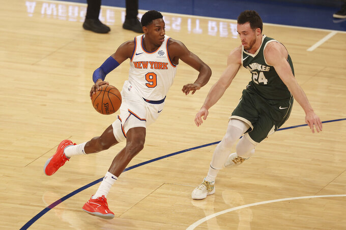 RJ Barrett, left, of the New York Knicks drives towards the basket against Pat Connaughton, right, of the Milwaukee Bucks at Madison Square Garden on Sunday, Dec. 27, 2020, in New York. (Mike Stobe/Pool Photo via AP)