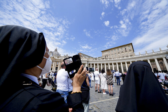 A nun takes pictures as Pope Francis recites the Angelus noon prayer from the window of his studio overlooking St.Peter's Square, at the Vatican, Sunday, May 30, 2021. (AP Photo/Andrew Medichini)