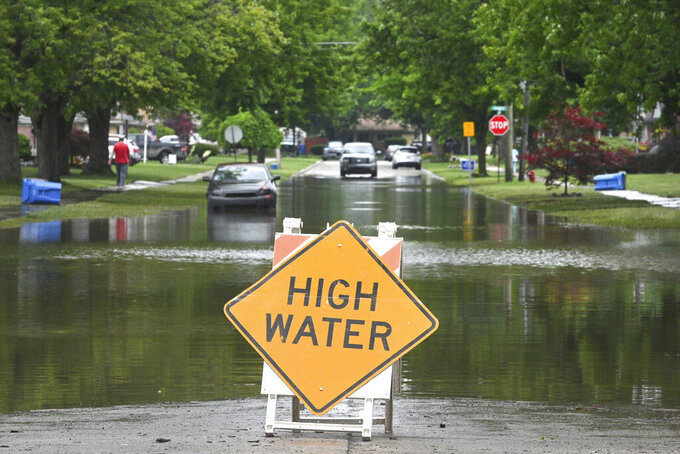 FILE - In this Saturday, June 26, 2021, file photo, a sign warns of high water in a Detroit neighborhood. A regional water authority board has formed a committee to look at the agency's response to last month's heavy rainfall that led to basement and street flooding in Detroit and some surrounding suburbs. (Max Ortiz/Detroit News via AP)