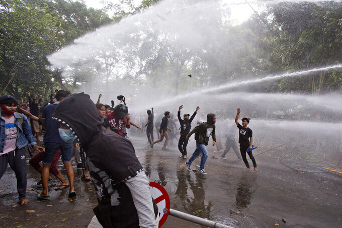 Protesters react as police use a water cannon to disperse them during a rally against a controversial bill on job creation in Medan, North Sumatra, Indonesia, Thursday, Oct. 8, 2020. Thousands of enraged students and workers staged rallies across Indonesia on Thursday in opposition to the new law they say will cripple labor rights and harm the environment. (AP Photo/Binsar Bakkara)