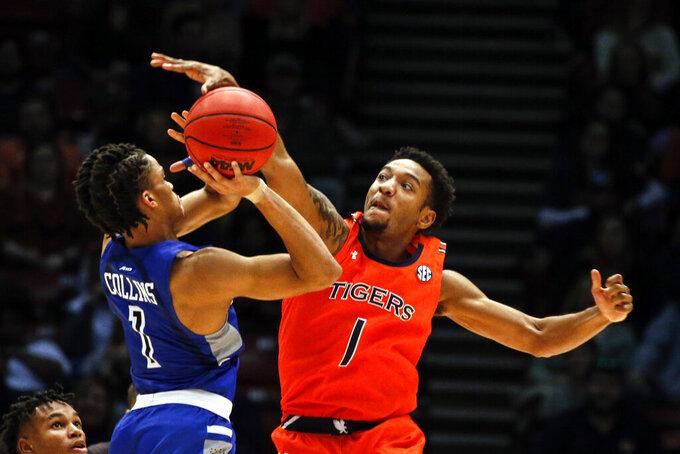 Auburn guard Jamal Johnson (1) blocks the shot of Saint Louis guard Yuri Collins (1) during the second half of an NCAA college basketball game Saturday, Dec. 14, 2019, in Birmingham, Ala. (AP Photo/Butch Dill)