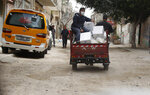 Palestinian workers distribute food supplies from the United Nations Relief and Works Agency (UNRWA) for impoverished refugee families after a three-week delay caused by fears of the coronavirus, at the Sheikh Redwan neighborhood of Gaza City, Tuesday, March 31, 2020. Gaza, which is blockaded by its neighbors Israel and Egypt, has only detected a few cases of coronavirus, with all of them confined to quarantine centers. But international officials fear the virus could quickly spread in the densely populated area, whose overburdened health system is not equipped to deal with a large outbreak. (AP Photo/Adel Hana)