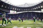 New York Jets players warm-up before an NFL football game between the New York Jets and the Atlanta Falcons at the Tottenham Hotspur stadium in London, England, Sunday, Oct. 10, 2021. (AP Photo/Ian Walton)