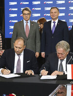 Poland's President Andrzej Duda, rear right, and U.S. Energy Secretary Rick Perry, rear left, look on as U.S. gas company Chenier Vice-President for Trade, Anatol Feygin,front left, and President of Poland's PGNiG gas company Piotr Wozniak,front right, sign a long-term deal for U.S. liquefied gas deliveries to Poland,in Warsaw, Poland, Thursday, Nov. 8, 2018. (AP Photo/Czarek Sokolowski)