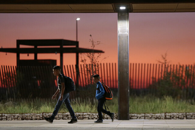 In this May 27, 2020 photo, Columbus Elementary School students walk alone across the the new port of entry between Columbus and Palomas as the sun rises behind them. A new Columbus port of entry, designed by Corpus Christi, Texas-based Richter Architects, has earned recognition from the American Institute of Architects and Texas Society of Architects. (Mark Lambie/The El Paso Times via AP)