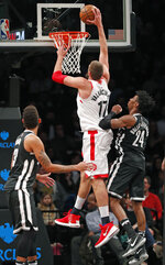 Toronto Raptors center Jonas Valanciunas (17) dunks over Brooklyn Nets forward Rondae Hollis-Jefferson (24) during the second half of an NBA basketball game, Tuesday, March 13, 2018, in New York. The Raptors defeated the Nets 116-102. (AP Photo/Kathy Willens)