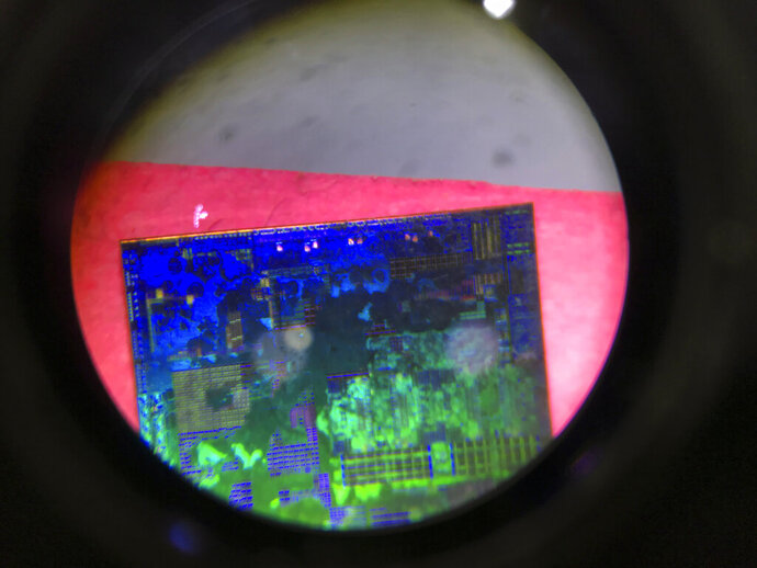 FILE - In this file photo taken Thursday, May 17, 2018, a Chinese microchip is seen through a microscope set up at the booth for the state-controlled Tsinghua Unigroup project which is driving China's semiconductor ambitions during the 21st China Beijing International High-tech Expo in Beijing, China. China is cutting taxes on its fledgling software and integrated circuit industries to spur development in the face of U.S. export controls that threaten to handicap Chinese tech companies. (AP Photo/Ng Han Guan, File)