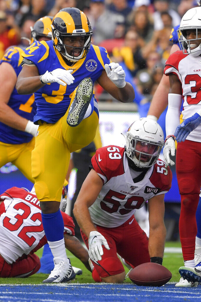 Los Angeles Rams running back Malcolm Brown celebrates after scoring as Arizona Cardinals linebacker Joe Walker looks on during first half of an NFL football game Sunday, Dec. 29, 2019, in Los Angeles. (AP Photo/Mark J. Terrill)
