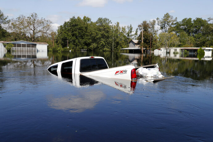 A submerged truck sits in floodwaters in the aftermath of Hurricane Florence in Nichols, S.C., Friday, Sept. 21, 2018. Virtually the entire town is flooded and inaccessible except by boat, just two years after it was flooded by Hurricane Matthew. (AP Photo/Gerald Herbert)